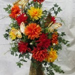 Silk Spider Mums in orange, yellow, red with golden butterflies make a great fall arrangement.