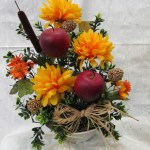 Fall arrangement mixed with red apples, cat tails, ivy, fall spider mums with an accent of a raffia bow.